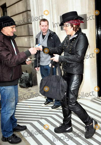 Adam Ant Photo - Wearing an all-black outfit complete with a top hat accented with two playing cards one of himself and one of Boy George rocker Adam Ant signs autographs for fans as he leaves BBC Radio 2 London UK 4111