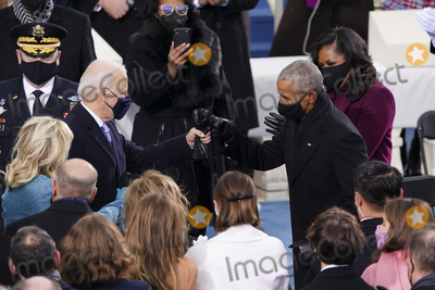 Barack Obama Photo - US President-elect Joe Biden left greets former US President Barack Obama right with a fist bump during the 59th presidential inauguration in Washington DC US on Wednesday Jan 20 2021 Biden will propose a broad immigration overhaul on his first day as president including a shortened pathway to US citizenship for undocumented migrants - a complete reversal from Donald Trumps immigration restrictions and crackdowns but one that faces major roadblocks in Congress Photographer Kevin DietschUPIAdMedia