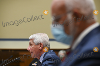 The National Photo - Anthony Fauci director of the National Institute of Allergy and Infectious Diseases speaks as Robert Redfield director of the Centers for Disease Control and Prevention (CDC) right listens during a House Select Subcommittee on the Coronavirus Crisis hearing in Washington DC US on Friday July 31 2020 Trump administration officials are set to defend the federal governments response to the coronavirus crisis at the hearing hosted by a House panel calling for a national plan to contain the virus Credit Erin Scott  Pool via CNPAdMedia