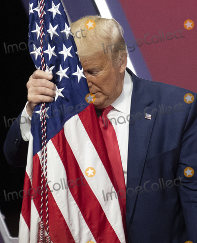American Flag Photo - United States President Donald J Trump rests his head on the American Flag after speaking at the Conservative Political Action Conference (CPAC) at the Gaylord National Resort and Convention Center in National Harbor Maryland on Saturday February 29 2020Credit Ron Sachs  CNPAdMedia
