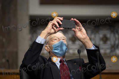 The Used Photo - United States Senator Chuck Grassley (Republican of Iowa) takes a cell phone photo of the empty Democratic Senators seats on the US Senate Judiciary Committee as they boycott the committee vote on Amy Coney Barrett to serve as an associate justice on the Supreme Court of the United States during a Senate Judiciary Committee Executive Business meeting in Washington on Thursday October 22 2020 Credit Caroline Brehman  Pool via CNPAdMedia
