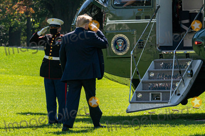White House Photo - United States President Donald J Trump salutes the Marine Guard as he boards Marine One on the South Lawn of the White House on Thursday October 15 2020 Trump will deliver remarks at a Fundraising Committee Reception in Doral Florida and participate in a Live NBC News Town Hall Event   Credit Ken Cedeno  Pool via CNP