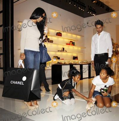 Aoki Lee Photo - EXCLUSIVE Model and former creative director of Phat Fashions Kimora Lee Simmons shops at Chanel on Robertson Blvd with her two daughters Ming Lee and Aoki Lee Simmons  While in the shop Kimora ex-wife of Russell Simmons chatted on her cell phone and appeared to try out her new purchases as she wore a Chanel bag on her shoulder and gold boots inside but left wearing tan heels and carrying a Hermes Birken tote  Ming 10 and Aoki 8 who showed their opposite fashion sense both seemed to enjoy their time shopping especially when they got to play with a little chihuahua puppy before leaving Los Angeles CA 011511Fees must be agreed prior to publication